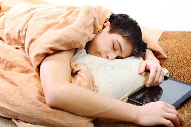 Tonåringen sover med minnestavladatoren arkivbild