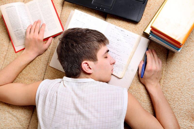 Tonåringen sover på böckerna arkivbilder
