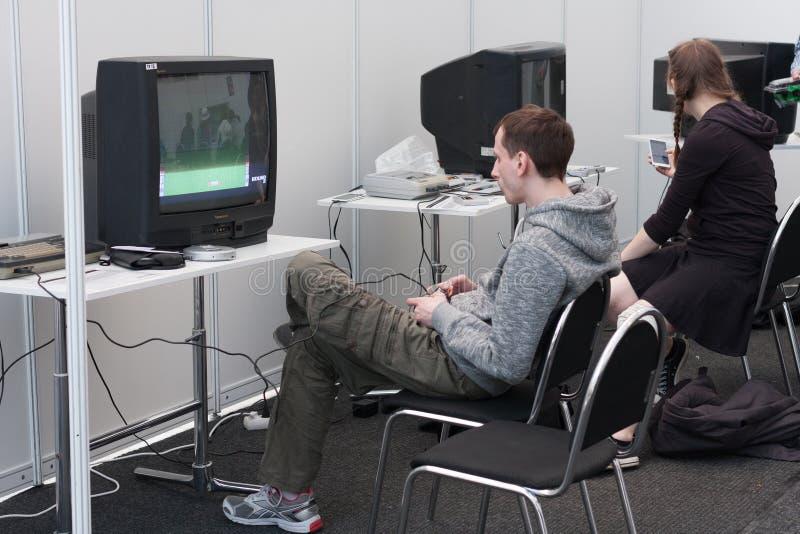 Tonåringen spelar dobbelkonsolen med television på Animefest royaltyfria bilder