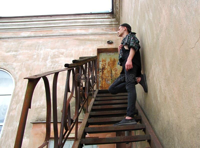 Tonåringen står på trappan av en övergiven byggnad royaltyfria foton