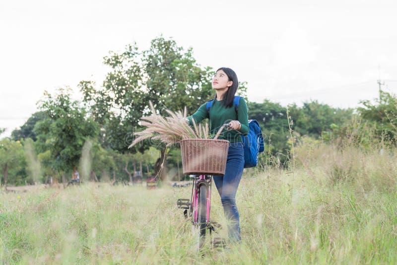 Tonåringflicka, cykel med blommakorgen i utomhus- landskap royaltyfria foton