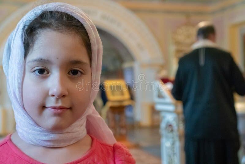 Tonåringflicka i en halsduk i en ortodox tempel Prästen läser böner Ritualen av det kristna dopet i kyrkan royaltyfri bild