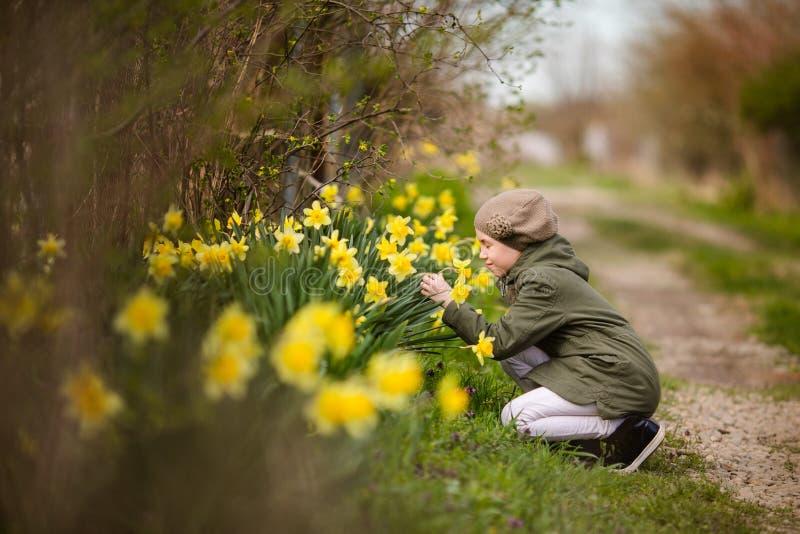 Tonåringflicka i grönt omslag och kaki- basker nära påskliljorna & x27en; trädgård i landet Vårlantgård och påsktema royaltyfri fotografi