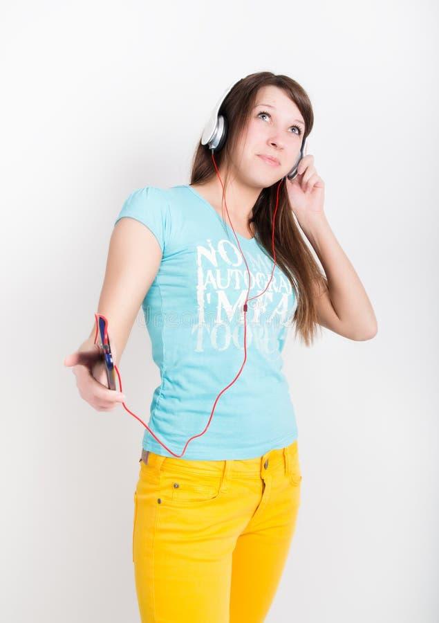 Tonåringflicka i gula flåsanden som lyssnar till musik från din smartphone royaltyfri fotografi