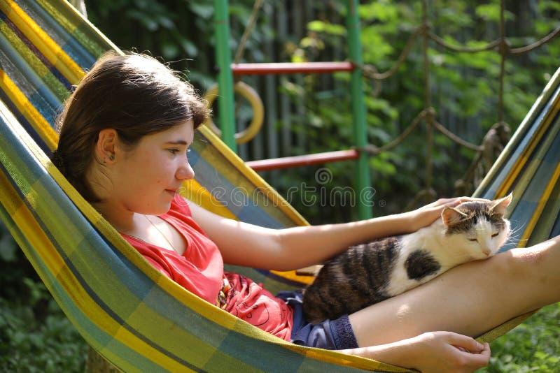Tonåringflicka i hängmatta med kattslut upp sommarfotoet royaltyfria foton