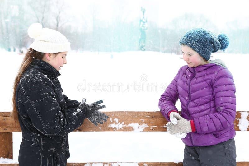Tonåringflicka i vinterisisbana i stack hattar och gryningomslag royaltyfri bild