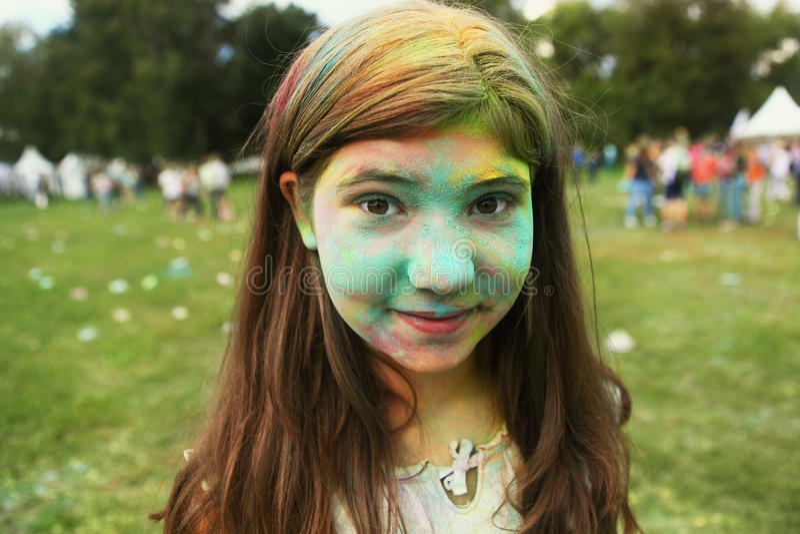 Tonåringflicka med den målade framsidan på holifärgfest fotografering för bildbyråer