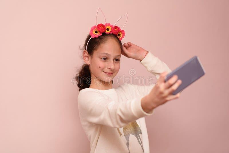 Tonåringflicka med diademen av blommor som tar selfie med hennes mobiltelefon på rosa bakgrund royaltyfria foton