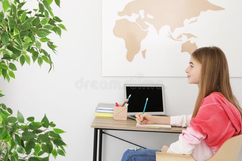 Tonåringflicka som gör hennes läxa royaltyfria bilder