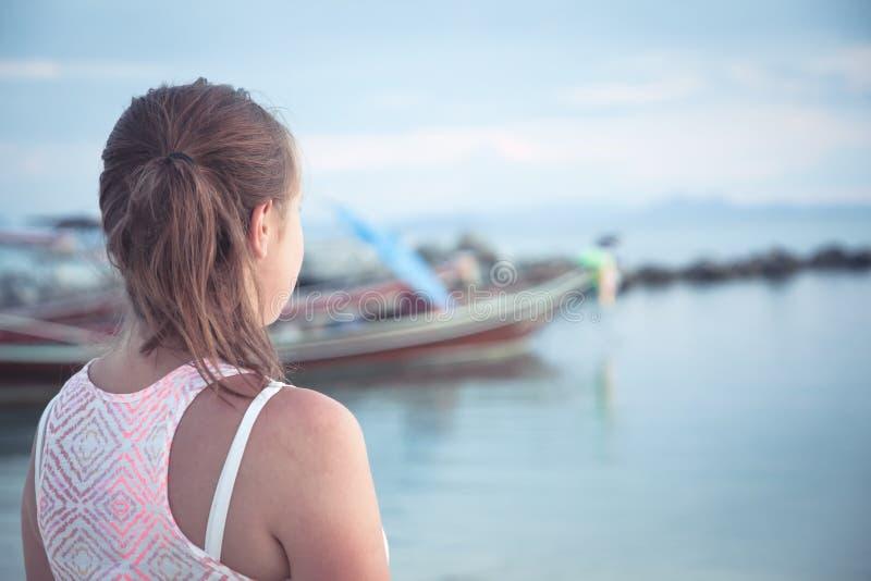 Tonåringflicka som ser in i avståndet på den tropiska stranden på solnedgången under sommarferier royaltyfri foto
