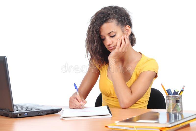 Tonåringflicka som studerar på ett skrivbord arkivfoton