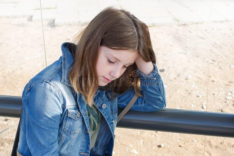 Tonåringflickan är ledsen att upprivet förvirrat se ner har ett problem arkivbild