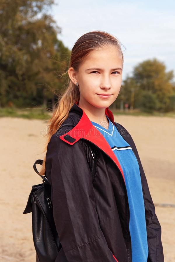 Tonåringflickan i en regnrock och ryggsäcken går utomhus royaltyfria foton