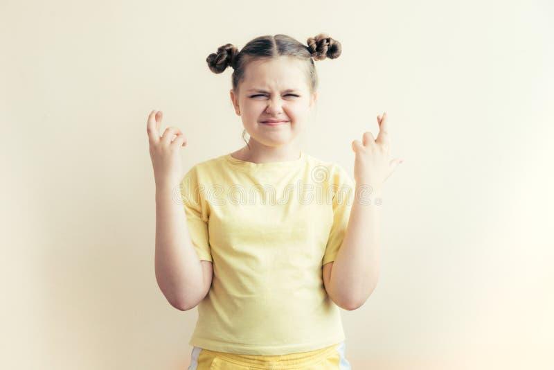 Tonåringflickan korsade hennes fingrar och pressade instängd förväntan för ögon av lycka royaltyfri foto