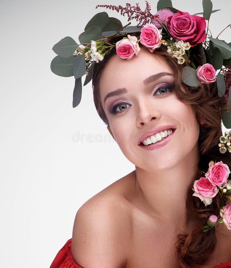 Tonåringflickan med trevlig makeup bär den vita blusen och röda rosor arkivbild
