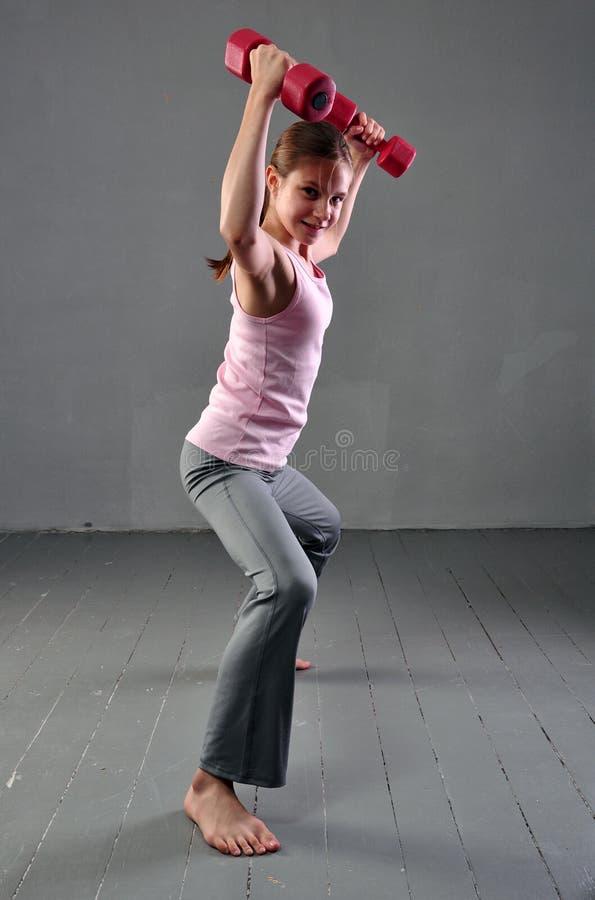Tonåringflickan som gör övningar med hantlar för att framkalla med hantlar, tränga sig in på grå bakgrund Full längdstående av to arkivbilder