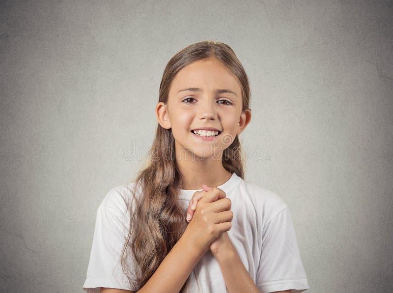Tonåringflickan som gör en gest med knäppte fast händer som är nätta behar arkivbilder
