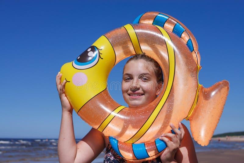 Tonåringflickastående i den uppblåsbara leksaksimningcirkeln arkivfoton