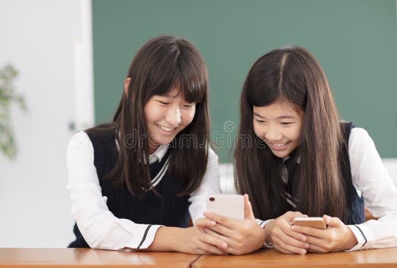 Tonåringflickastudent som håller ögonen på den smarta telefonen i klassrum arkivbild