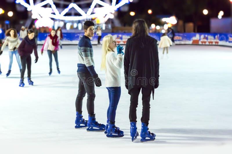 Tonåringflickor och pojke som åker skridskor på isisbana royaltyfri foto