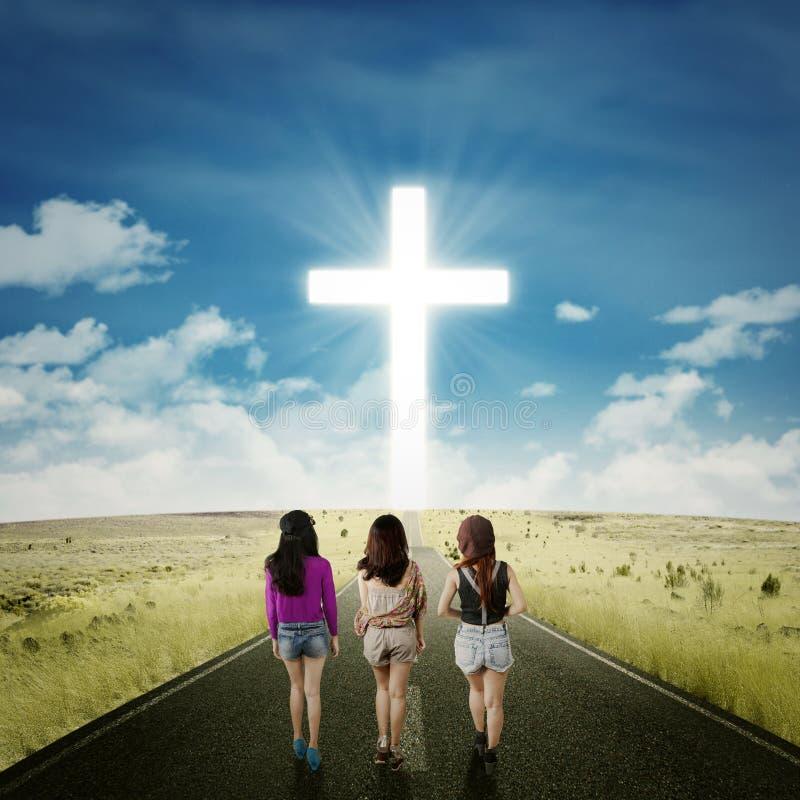 Tonåringflickor på vägen med ett kors arkivfoton