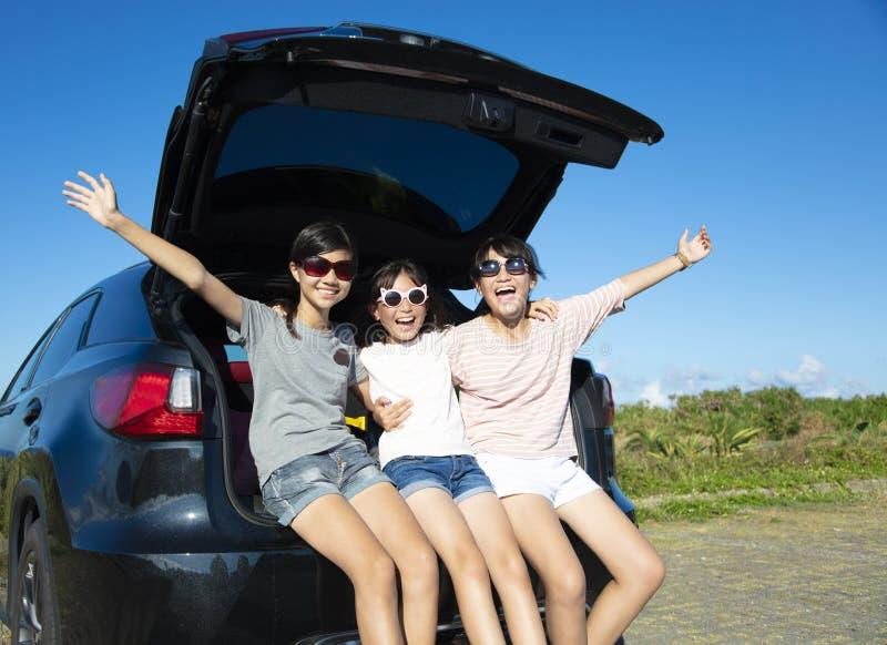 Tonåringflickor som har gyckel i vägtur på sommar arkivfoton