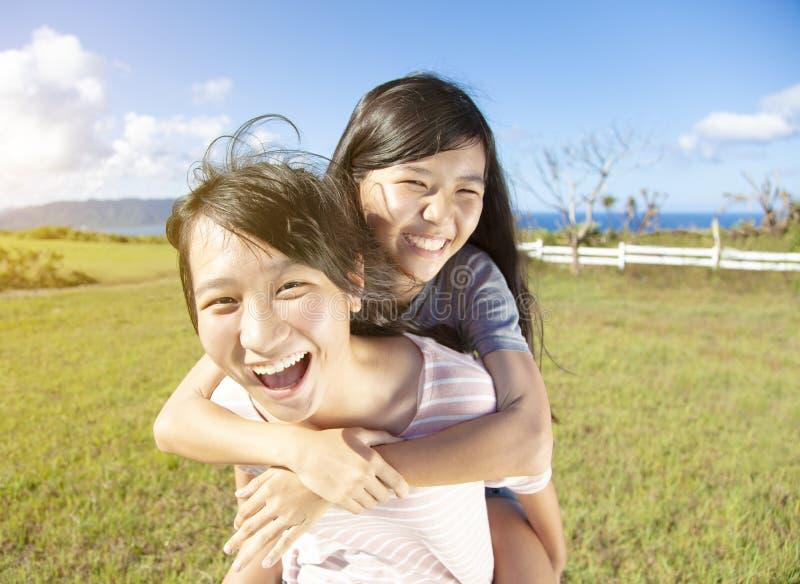 Tonåringflickor som på ryggen spelar och har gyckel royaltyfri bild