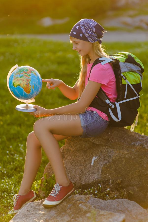 Tonåringhandelsresande med ryggsäckar som sitter på, vaggar Reslustloppbegrepp royaltyfria bilder
