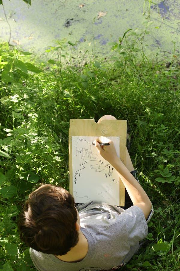 Tonåringkonstnärpojken gör utkastet att skissa av dammsjö n royaltyfri bild