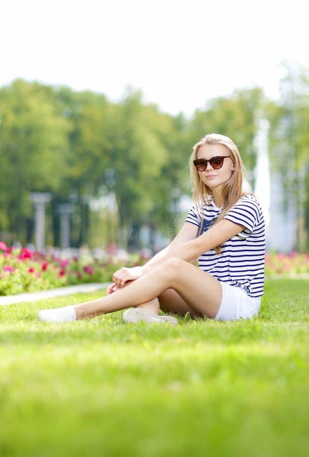 Tonåringlivsstilbegrepp Gulligt och le den Caucasian blonda tonårs- flickan med Longboard i grön sommar parkera arkivfoto
