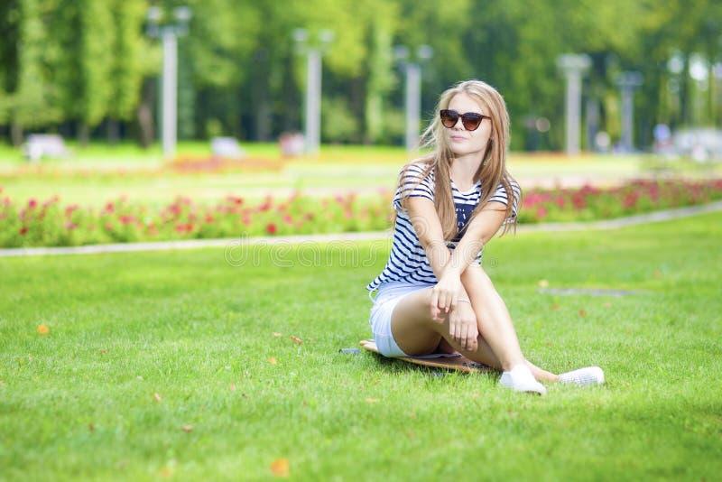 Tonåringlivsstilbegrepp Ståenden av den gulliga och positiva Caucasian blonda tonåringflickan som poserar på Longboard i grön som fotografering för bildbyråer