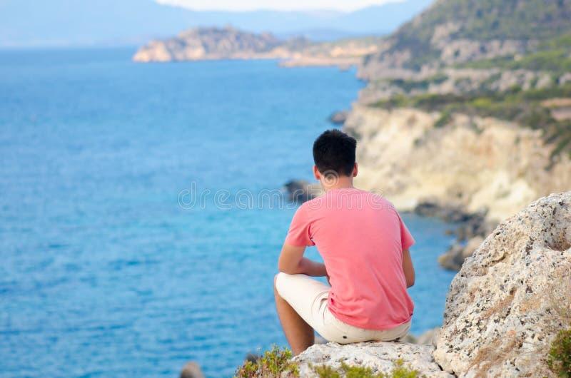 Tonåringmannen sitter melankoliskt vaggar på på stranden nära det djupblå havet arkivbild