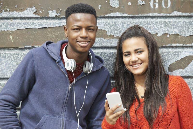 Tonåringpar som delar textmeddelandet på mobiltelefonen arkivbilder