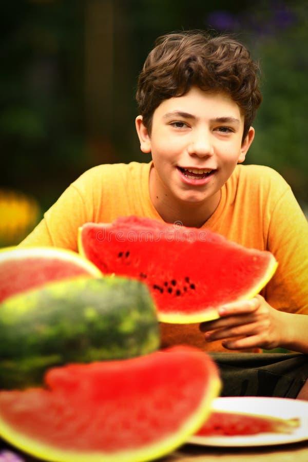 Tonåringpojke med slut för snittvattenmelon upp fotoet arkivbilder