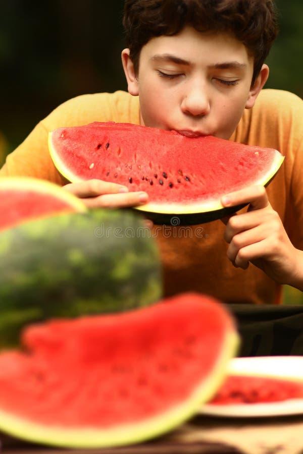 Tonåringpojke med slut för snittvattenmelon upp fotoet fotografering för bildbyråer