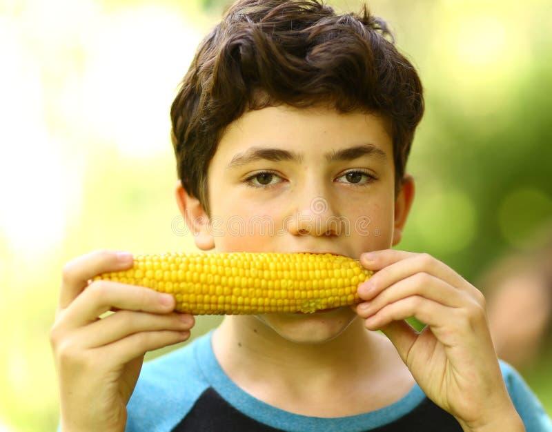 Tonåringpojke som äter kokt slut för havremajskolv upp fotoet royaltyfri bild