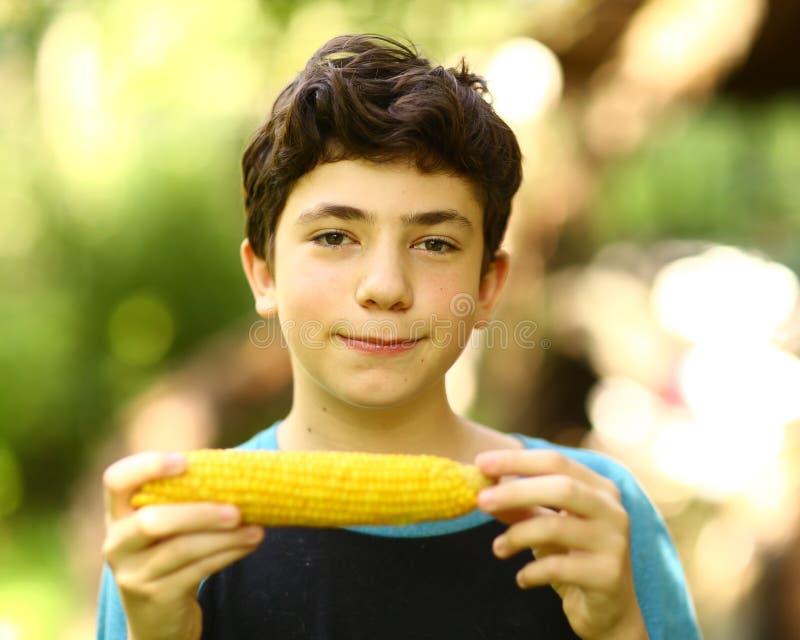 Tonåringpojke som äter kokt slut för havremajskolv upp fotoet arkivbild
