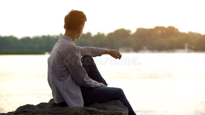 Tonåringpojke som tycker om den härliga sikten som sitter på den stora stenen nära floden som vilar royaltyfri bild