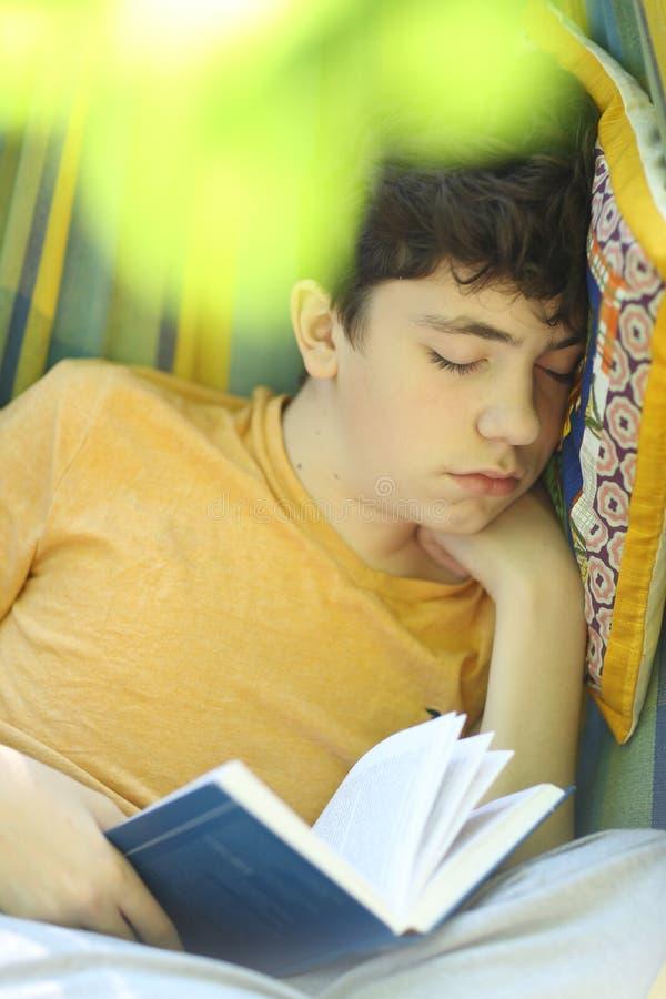 Tonåringpojke som vilar sömn med boken i hängmatta på grön trädgård för sommar arkivfoton