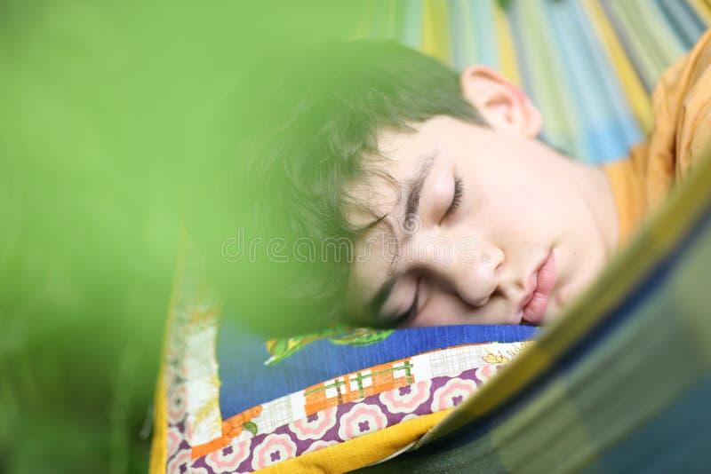 Tonåringpojke som vilar sömn med boken i hängmatta på grön trädgård för sommar arkivbilder