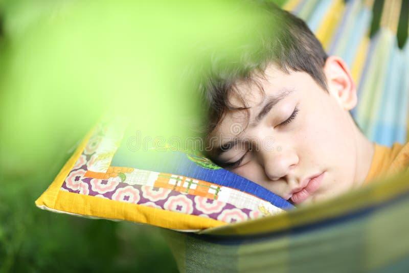 Tonåringpojke som vilar sömn med boken i hängmatta på grön trädgård för sommar royaltyfri bild