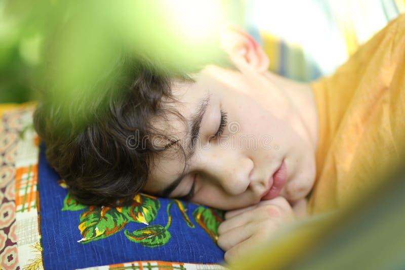 Tonåringpojke som vilar sömn med boken i hängmatta på grön trädgård för sommar royaltyfri fotografi