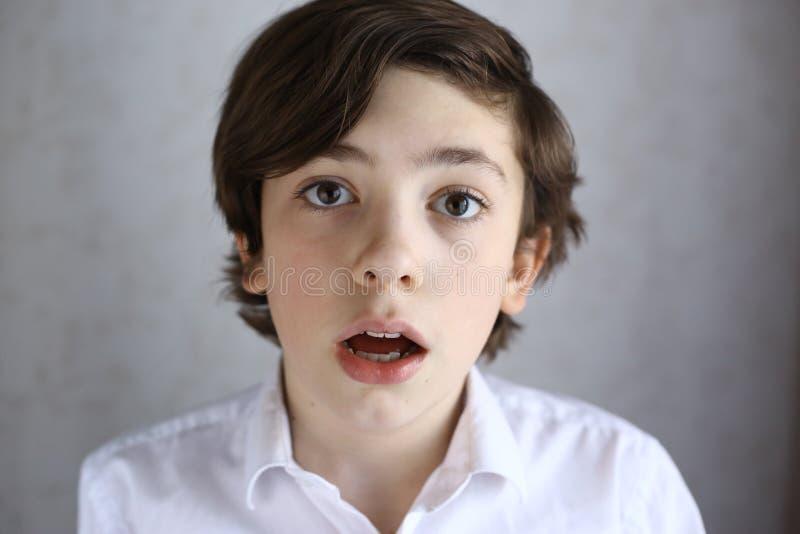 Tonåringpojkeframsida med överraskninguttryck royaltyfria foton