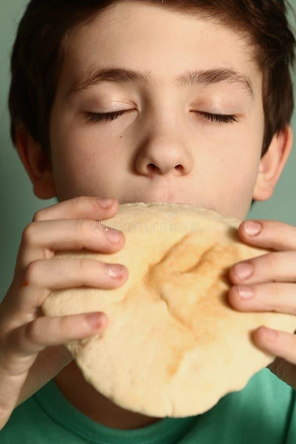 Tonåringpojkeslutet synar äta nytt tortillabröd arkivfoto