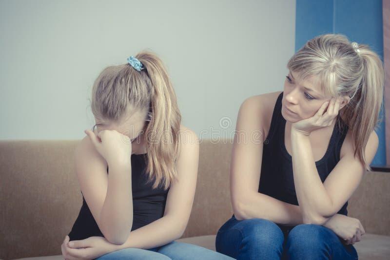 Tonåringproblem - ledsen skriande tonårs- flicka och hennes bekymrade moder royaltyfri foto