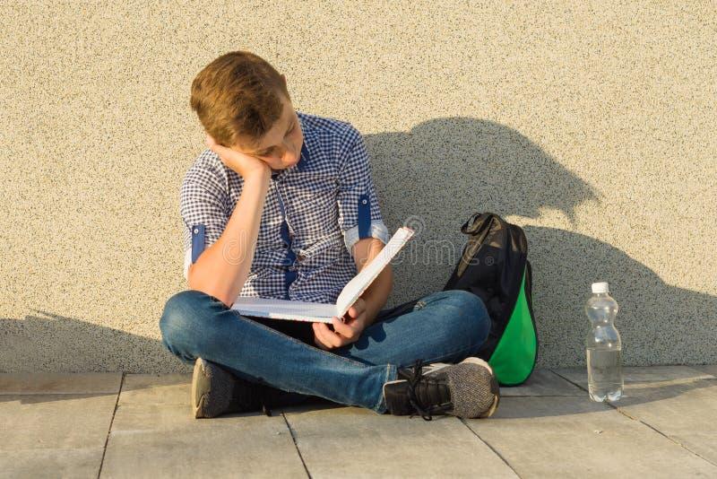Tonåringskolpojken läser läroboken, sitter nära den gråa väggen av skolan fotografering för bildbyråer