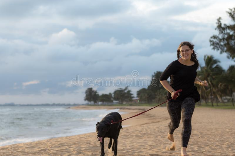 Tonåringspring med hennes hund på stranden arkivbilder