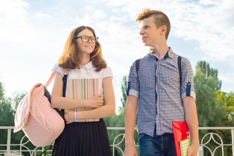 Tonåringstudenter med ryggsäckar, läroböcker, går till skolan Utomhus- stående av tonårs- pojke och flicka 14, 15 gamla år royaltyfria bilder