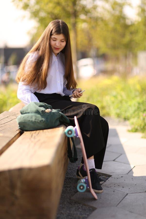 Tonåringstudentflicka med lång brun ritt på pennyboardslut u arkivfoton