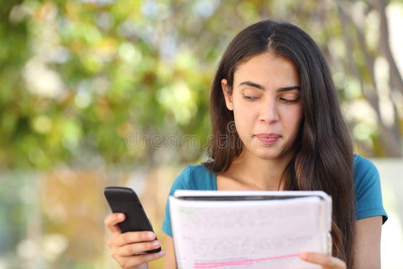 Tonåringstudentflicka som från sidan ser på mobiltelefonen, medan studera fotografering för bildbyråer